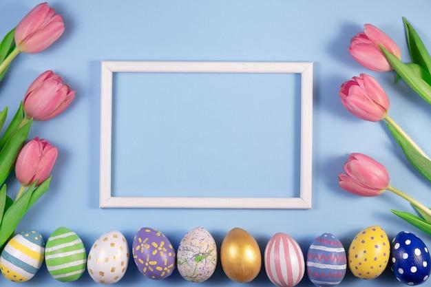 Tulpenbloemen en paaseieren met houten frame dat op blauw wordt geïsoleerd