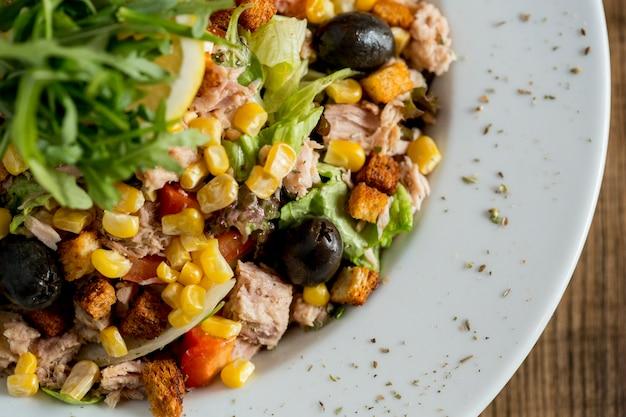 Tun salade met olijven, maïs en rucola