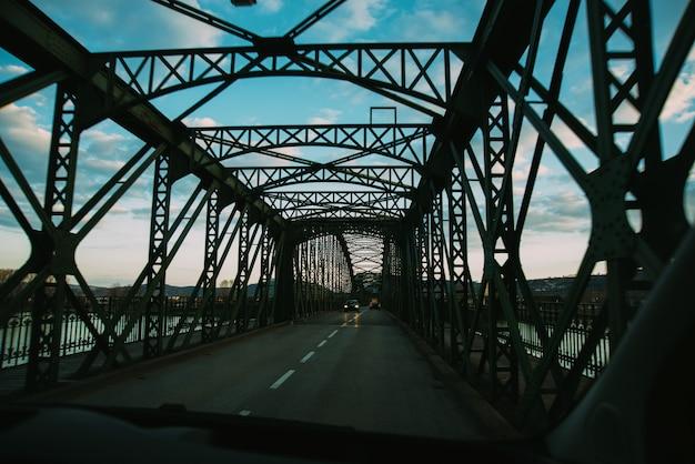 Tunel van een metalen brug voor auto's over een rivier.