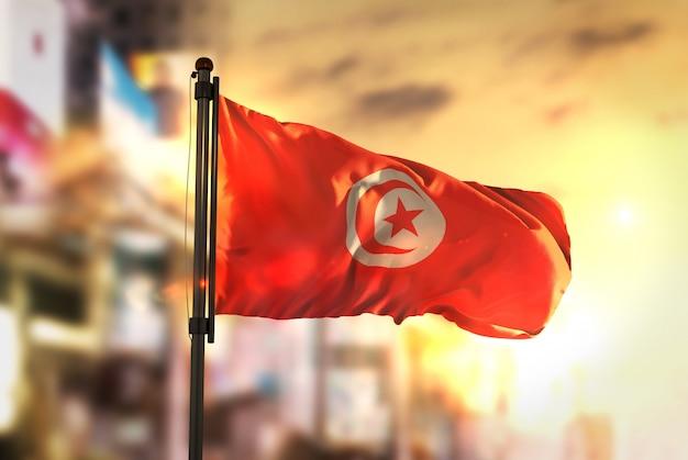 Tunesië vlag tegen stad wazige achtergrond bij zonsopgang achtergrondverlichting