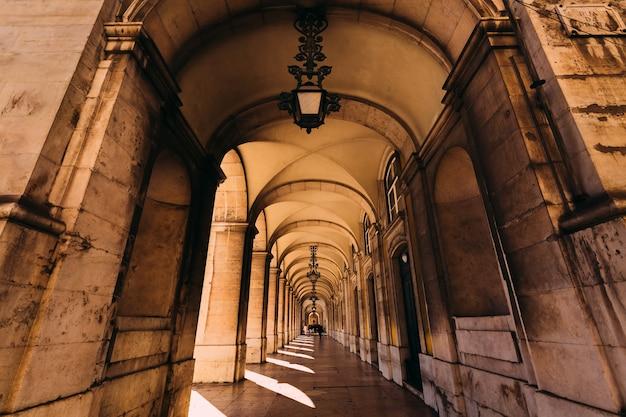 Tunnel van bogen tijdens een zomerse dag met zonlicht gooien gaten.