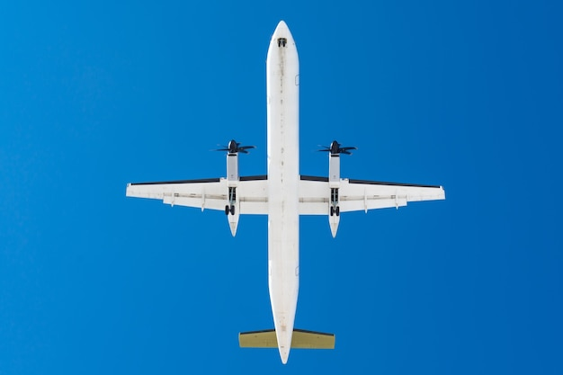 Turbopropvliegtuigen met propellermotoren op vleugels alvorens op een landingsbaan op de luchthaven tegen een blauwe hemel te landen.