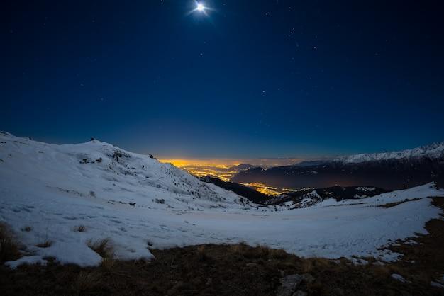 Turijn stadslichten, nacht uitzicht vanaf besneeuwde alpen bij maanlicht.