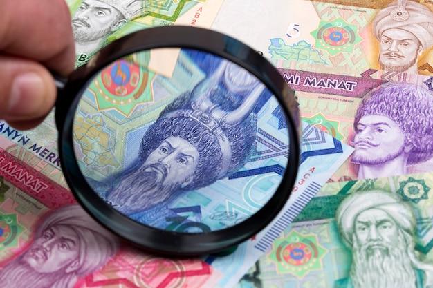 Turkmenistan manat in een vergrootglas een zakelijke achtergrond