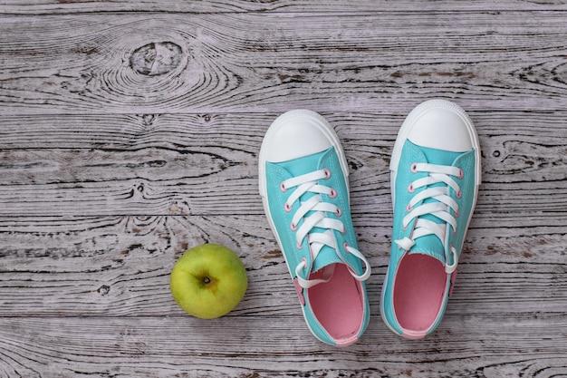 Turkoois met roze sneakers en een appel op de houten vloer.