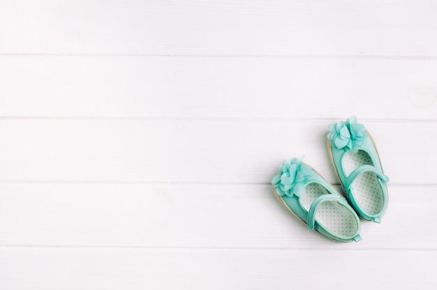 Turkoois schoenen voor babymeisje over lichte houten achtergrond met exemplaarruimte