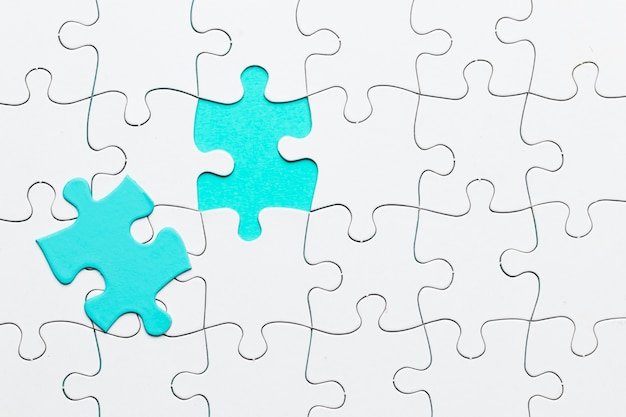 Turkoois stuk van puzzel op witte puzzelachtergrond