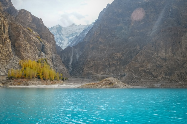Turkoois water van attabad-meer in de herfstseizoen tegen sneeuw afgedekte bergketen.