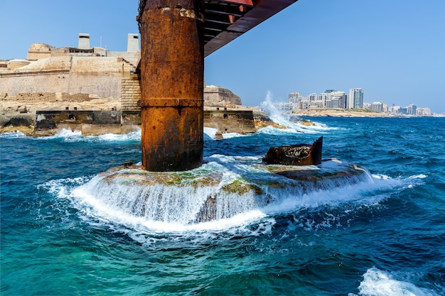 Turkooise golven van de middellandse zee botsen tegen de metalen steun van de st elmo-brug in malta, valletta.