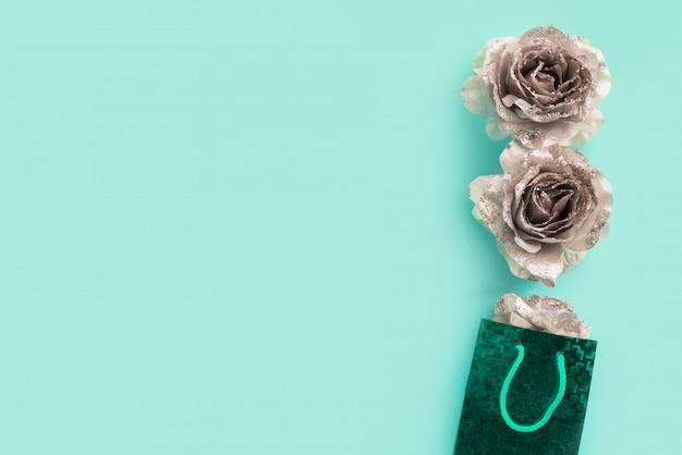 Turkooizen achtergrond voor tekst met zilveren glinsterende rozen.
