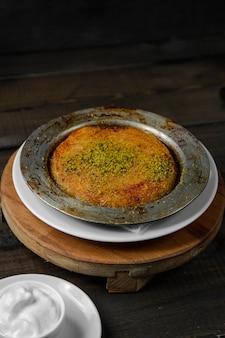 Turks dessert kunefe gegarneerd met pistache