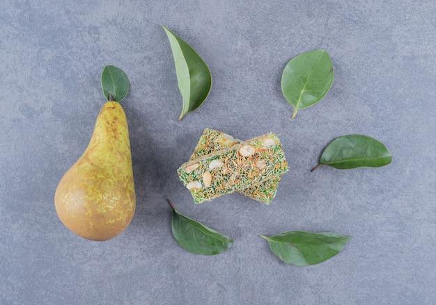 Turks fruit. lokum of rahat lokum met hazelnoten en peer op grijze achtergrond.