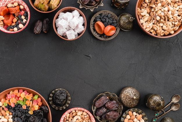 Turks fruit met gedroogde vruchten; noten; lukum en baklava op zwarte concrete achtergrond