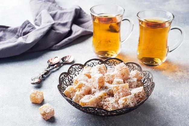 Turks fruit met hazelnoot in gebeeldhouwde metalen kom en thee in glazen beker