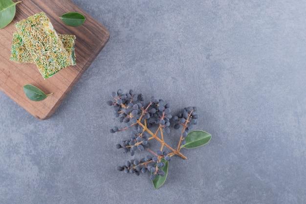 Turks fruit rahat lokum met hazelnoten op houten bord over grijze achtergrond.
