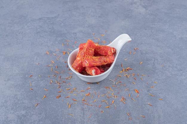 Turks fruit rahat lokum met pistachenoten en droge rozijnen op grijze achtergrond.