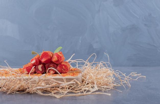 Turks fruit rahat lokum met pistachenoten op een houten bord.