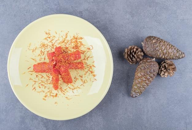 Turks fruit rahat lokum met pistachenoten op gele plaat.