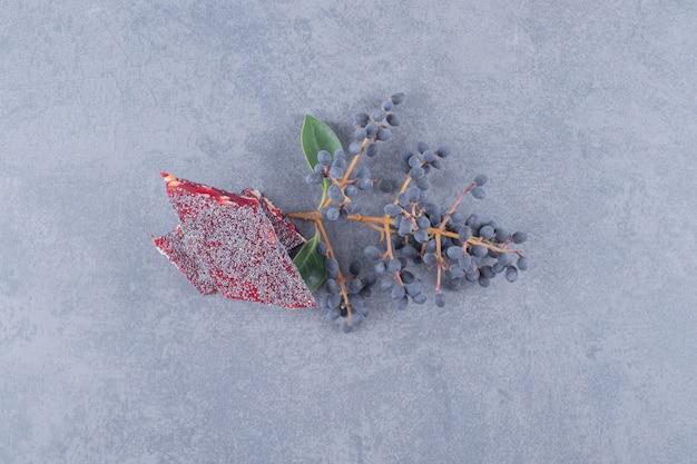 Turks fruit rahat lokum met pistachenoten op grijze achtergrond.