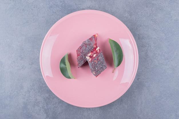 Turks fruit rahat lokum met pistachenoten op roze plaat.