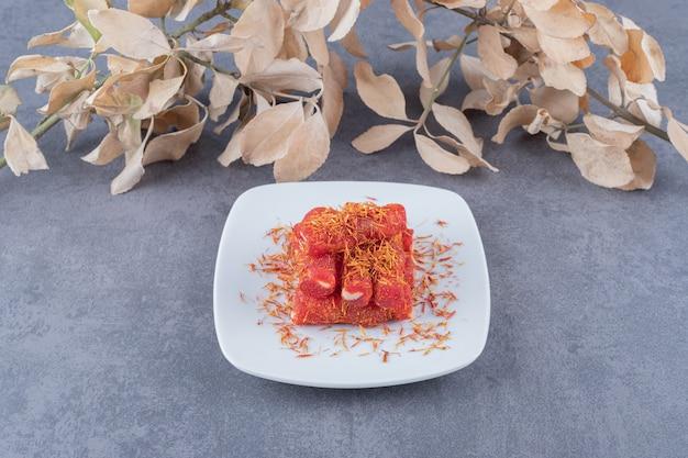 Turks fruit rahat lokum met pistachenoten op witte plaat.