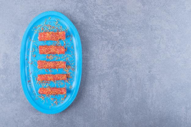 Turks fruit rahat lokum op blauwe houten bord over grijze achtergrond.