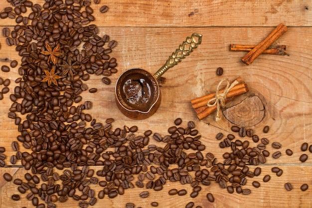 Turks koffiezetapparaat en koffiebonen op een rustieke houten tafel in een bovenaanzicht