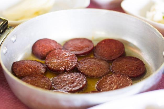Turks ontbijt. gebakken worst in een kleine koekenpan op de tafel