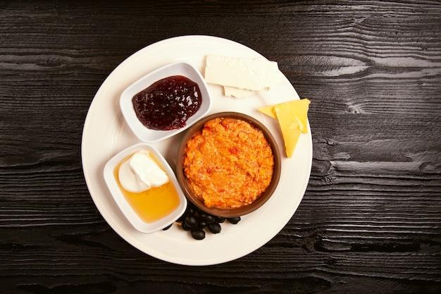 Turks ontbijt menemen met honing, room, olijven, jam en kaasvariaties in witte plaat en een glas thee