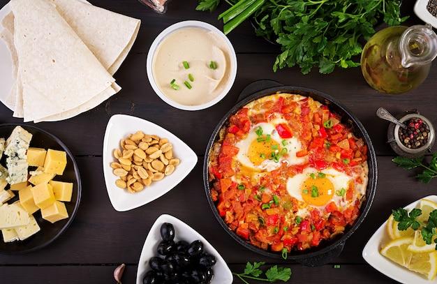 Turks ontbijt. shakshuka, olijven, kaas en fruit. rijke brunch.