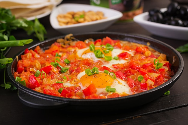 Turks ontbijt - shakshuka, olijven, kaas en fruit. rijke brunch.
