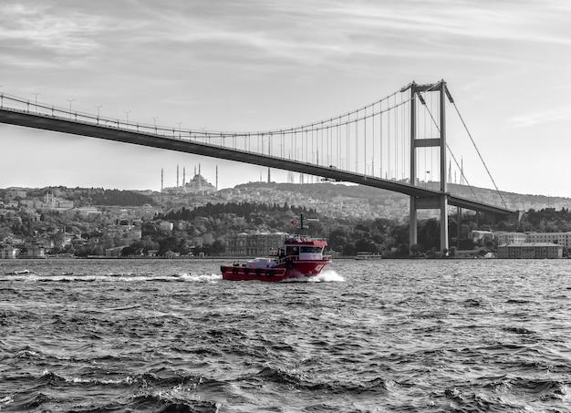 Turks schip onder de bosporus-brug van istanbul, vintage stijl.