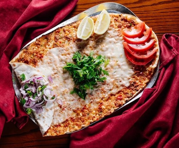 Turks straatvoedsel lahmacun met tomaat, citroen, peterselie en ui.
