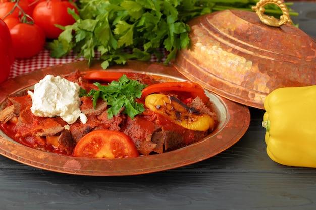 Turks vlees bak met groenten in koperen plaat close-up