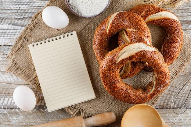 Turkse bagel met kladblok, eieren, deegrol bovenaanzicht op een zak doek en houten oppervlak