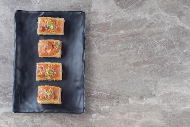 Turkse bakhlava's op een zwarte schotel op marmeren oppervlak