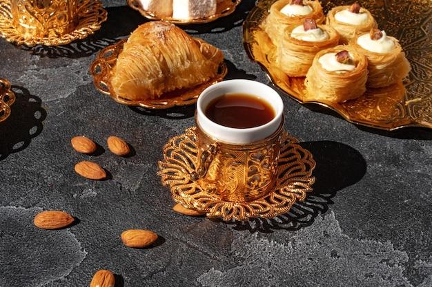 Turkse dessert baklava met een kopje koffie op zwarte achtergrond