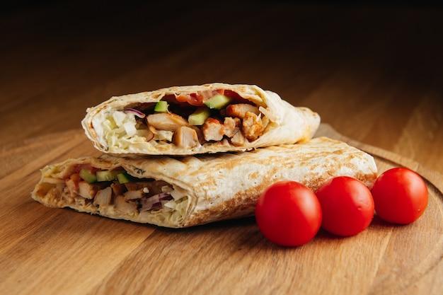 Turkse döner kebab met gegrild vlees. sappige shoarma op een houten bord
