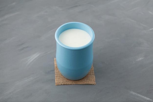 Turkse drank ayran of kefir in blauwe keramische kruik op grijs