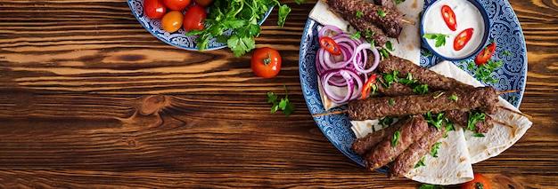 Turkse en arabische traditionele ramadan mix kebab plaat. kebab adana, kip, lam en rundvlees op lavashbrood met saus.