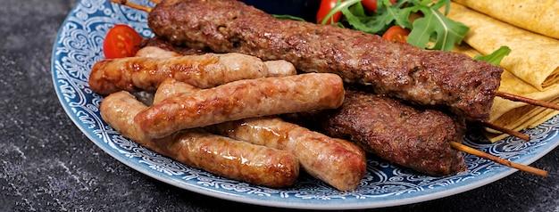 Turkse en arabische traditionele ramadan mix kebab plaat. kebab adana, lamsvlees en rundvlees op lavashbrood met tomatensaus.