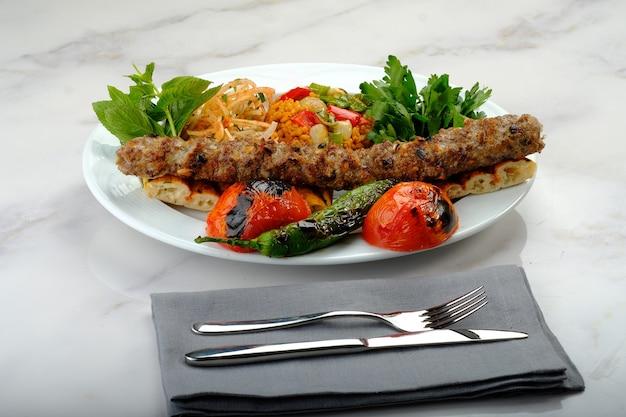 Turkse kebab klaar om aan tafel geserveerd te worden adana urfa kip shish gemengde kebab beyti