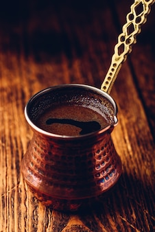 Turkse koffie. gebrouwen koffie in koperen cezve op houten oppervlak