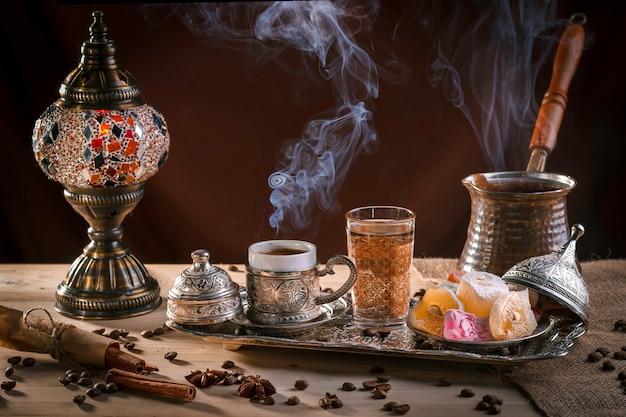 Turkse koffie in cezve en traditionele turkse verrukking. stoom boven een kopje. antieke lamp