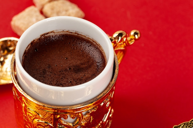 Turkse koffie in een gouden oosterse cup op rode achtergrond