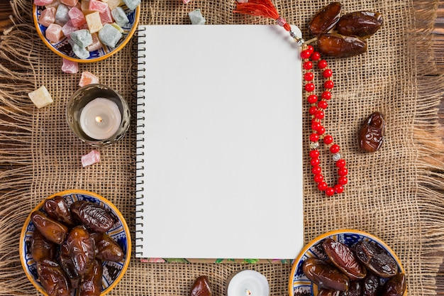 Turkse kom met sappige dadels; verrukking lukum met lege witte pagina en rode heilige parels op jutedoek