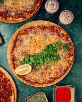 Turkse lahmacunpizza in tomatensaus met citroen en peterselie.