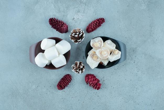 Turkse lekkernijen en marshmallows in kleine kommen naast dennenappels op marmer.
