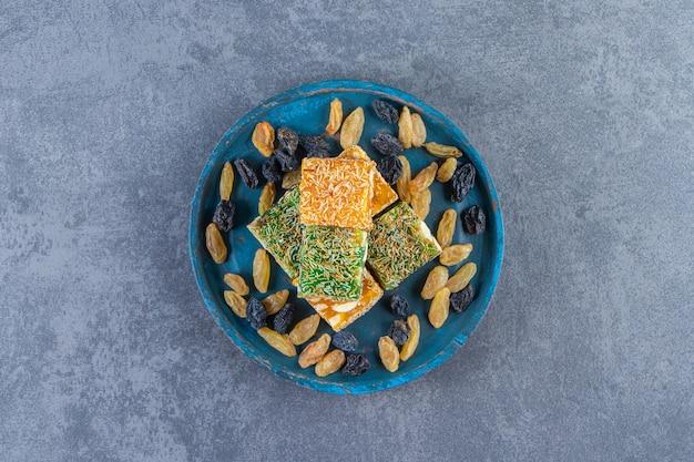 Turkse lekkernijen en rozijnen op een houten bord, op het marmeren oppervlak