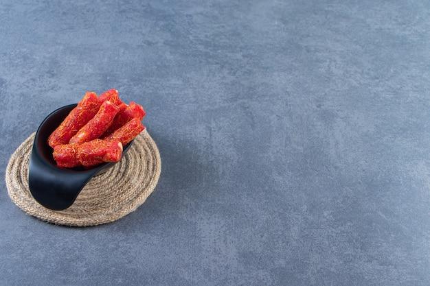 Turkse lekkernijen in een kom op een onderzetter, op het marmeren oppervlak